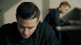 Retrato del funcionamiento hermoso joven del hombre, sentada en la tabla en oficina moderna metrajes