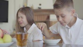 Retrato del gemelo del hermano y de la hermana que come las gachas de avena o los copos de maíz no sabrosos para el desayuno sin  almacen de metraje de vídeo