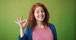 Retrato del gesto alegre de la AUTORIZACIÓN de la demostración de la estudiante que sonríe mirando la cámara almacen de video