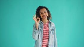 Retrato del gesto de mano ACEPTABLE de la demostración afroamericana alegre de la muchacha que mira la cámara metrajes