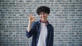 Retrato del gesto de mano alegre de la AUTORIZACIÓN de la demostración del inconformista que sonríe mirando la cámara almacen de video