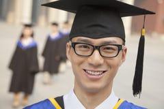 Retrato del graduado sonriente joven con los vidrios que llevan un birrete, mirando la cámara Imágenes de archivo libres de regalías