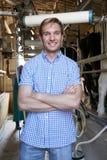 Retrato del granjero With Dairy Cattle en el ordeño vertido Imágenes de archivo libres de regalías