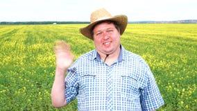 Retrato del granjero feliz que mano que agita y saludo alguien en el campo en un día soleado almacen de metraje de vídeo