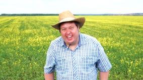 Retrato del granjero feliz que se coloca y ríe en el campo en un día soleado almacen de metraje de vídeo