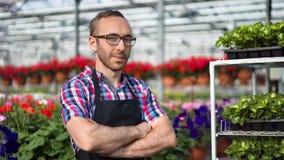 Retrato del granjero profesional de sexo masculino feliz que presenta en el invernadero que mira el primer medio de la cámara almacen de metraje de vídeo