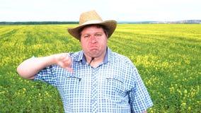 Retrato del granjero que muestra el pulgar abajo en el campo en un día soleado metrajes