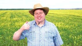 Retrato del granjero que muestra el pulgar encima del sombrero de vaquero del desgaste en el campo en un día soleado almacen de video