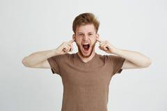 Retrato del griterío de grito de los oídos cerrados enojados emotivos jovenes del hombre sobre el fondo blanco Fotografía de archivo
