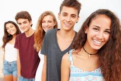Retrato del grupo adolescente que se inclina contra la pared Imágenes de archivo libres de regalías