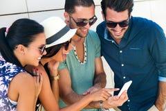 Retrato del grupo de amigos que se divierten con smartphones Foto de archivo libre de regalías