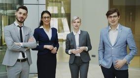 Retrato del grupo de hombres de negocios que hablan y de mirada entonces sonriente en cámara en pasillo moderno de la oficina den