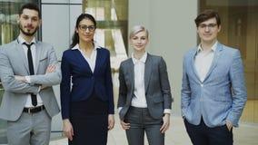Retrato del grupo de hombres de negocios que sonríen en oficina moderna Equipo de hombres de negocios y de empresarias que se une