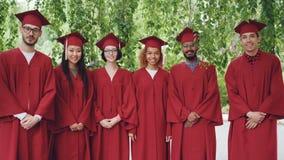 Retrato del grupo multiétnico de estudiantes de graduación que colocan los vestidos rojos al aire libre que llevan y de mortero-t almacen de metraje de vídeo