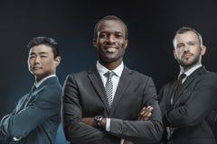 retrato del grupo multicultural de hombres de negocios en los trajes que miran la cámara foto de archivo