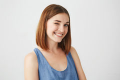 Retrato del guiño sonriente de la muchacha morena juguetona hermosa mirando la cámara sobre el fondo blanco Fotografía de archivo
