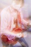 Retrato del guitarrista masculino Playing con la expresión Tirado con el St Foto de archivo