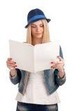 Mujer joven que lee la revista para mujer Foto de archivo