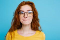 Retrato del Headshot de la muchacha roja del pelo del jengibre feliz con la cara divertida que mira la cámara Fondo azul en color Imagen de archivo libre de regalías