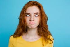 Retrato del Headshot de la muchacha roja del pelo del jengibre feliz con la cara divertida que mira la cámara Fondo azul en color Foto de archivo