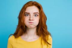 Retrato del Headshot de la muchacha roja del pelo del jengibre feliz con la cara divertida que mira la cámara Fondo azul en color Imágenes de archivo libres de regalías