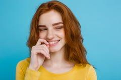Retrato del Headshot de la muchacha roja del pelo del jengibre feliz con las pecas que sonríe mirando la cámara Fondo azul en col Fotos de archivo