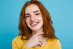 Retrato del Headshot de la muchacha roja del pelo del jengibre feliz con las pecas que sonríe mirando la cámara Fondo azul en col Fotografía de archivo libre de regalías