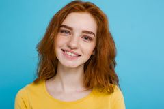Retrato del Headshot de la muchacha roja del pelo del jengibre feliz con las pecas que sonríe mirando la cámara Fondo azul en col Fotografía de archivo
