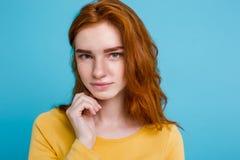 Retrato del Headshot de la muchacha roja del pelo del jengibre feliz con las pecas que sonríe mirando la cámara Fondo azul en col Imágenes de archivo libres de regalías