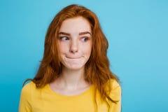 Retrato del Headshot de la muchacha roja del pelo del jengibre feliz con las pecas que sonríe mirando la cámara Fondo azul en col Imagenes de archivo