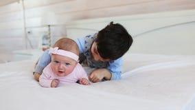 Retrato del hermano lindo con su pequeña hermana en una cama en casa metrajes