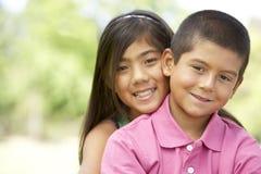 Retrato del hermano y de la hermana en parque Imágenes de archivo libres de regalías