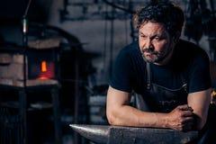 Retrato del herrero que se prepara para trabajar el metal en el yunque foto de archivo