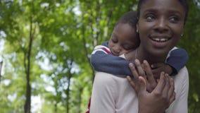 Retrato del hijo afroamericano adorable de la tenencia de la mujer en su parte posterior en el parque verde con los brazos separa almacen de metraje de vídeo