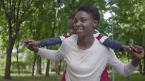 Retrato del hijo afroamericano de la tenencia de la mujer en su parte posterior en el parque verde con los brazos separados al ci metrajes