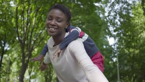 Retrato del hijo afroamericano lindo de la tenencia de la mujer en su parte posterior en el parque verde con los brazos separados almacen de video