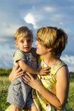 Retrato del hijo feliz el besarse y de la sacudida de la mamá en jardín verde del verano Bebé de abarcamiento de la madre linda q Imagen de archivo