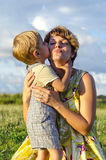Retrato del hijo feliz el besarse y de la sacudida de la mamá en jardín verde del verano Bebé de abarcamiento de la madre linda q Imagenes de archivo