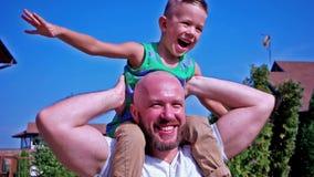 Retrato del hijo y del padre, niño que se sienta en los hombros de su familia feliz del papá que tiene risa de la diversión almacen de video