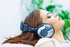 Retrato del hogar de la mujer joven Muchacha durmiente con los auriculares Imagen de archivo