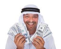 Retrato del hombre árabe maduro que lleva a cabo dólares Imagen de archivo