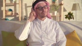Retrato del hombre árabe que escucha la música con los auriculares almacen de metraje de vídeo