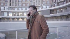 Retrato del hombre acertado atractivo en la situación marrón de la capa en la calle de la ciudad que habla por el teléfono móvil  almacen de metraje de vídeo
