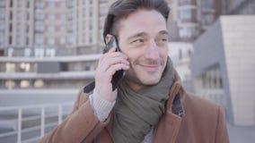 Retrato del hombre acertado hermoso en la situación marrón de la capa en la calle de la ciudad que habla por el teléfono móvil Pa almacen de video