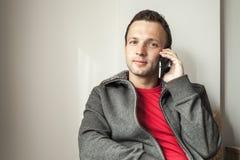 Retrato del hombre adulto joven que habla en el teléfono móvil Fotos de archivo libres de regalías