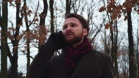 Retrato del hombre adulto que habla por el teléfono celular en el parque del invierno El caballero solo pasa tiempo al aire libre almacen de video
