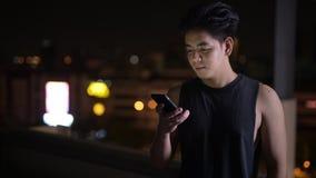 Retrato del hombre asiático feliz joven que usa el teléfono al aire libre en la noche almacen de video