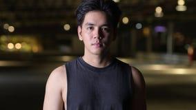 Retrato del hombre asiático hermoso feliz joven que sonríe al aire libre en la noche almacen de metraje de vídeo