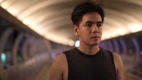 Retrato del hombre asiático hermoso joven que piensa al aire libre en la noche almacen de metraje de vídeo