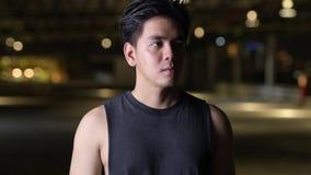 Retrato del hombre asiático hermoso joven que piensa al aire libre en la noche almacen de video